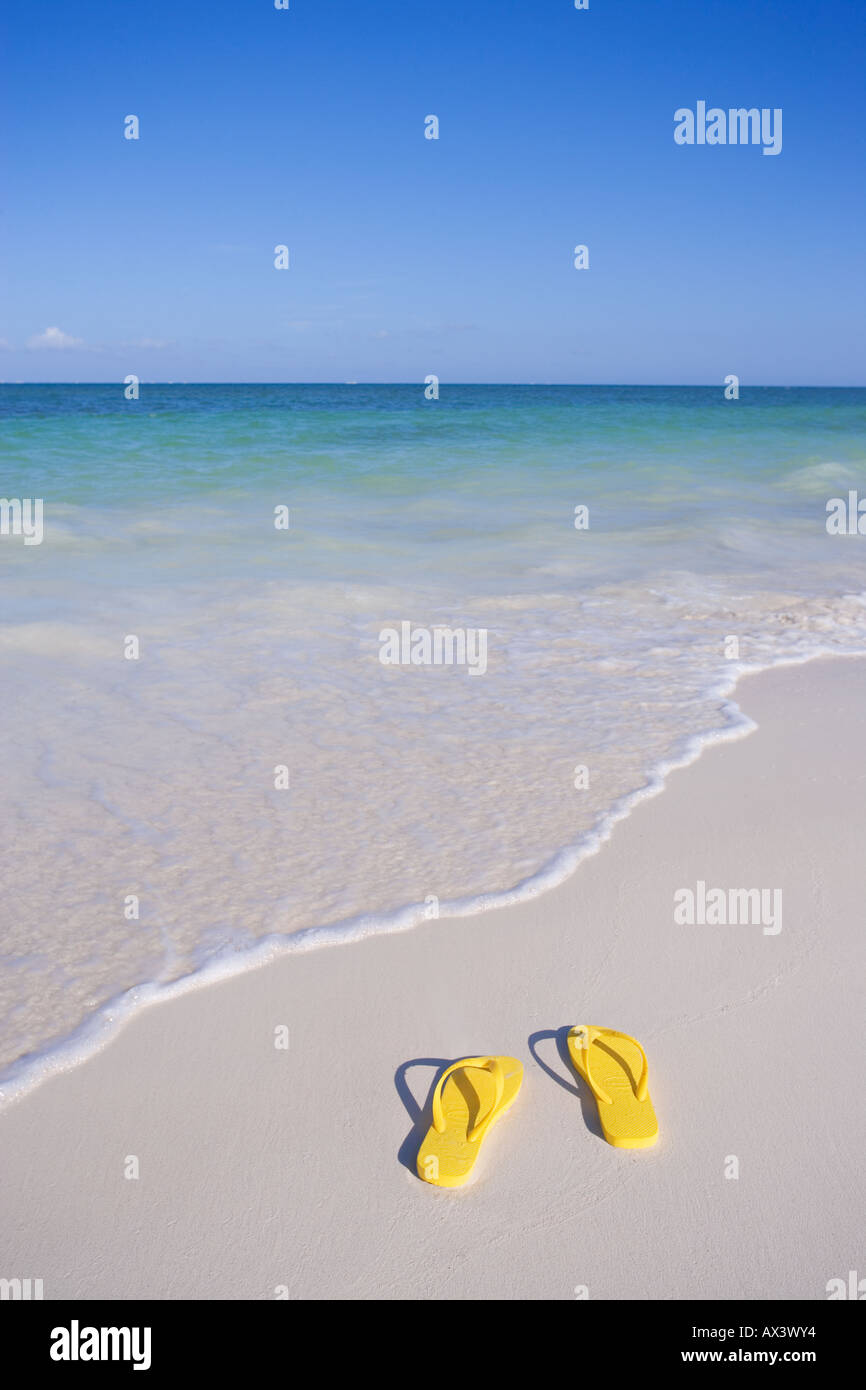 pair of yellow flip flop sandals on beach at waters edge in the Caribbean - Stock Image