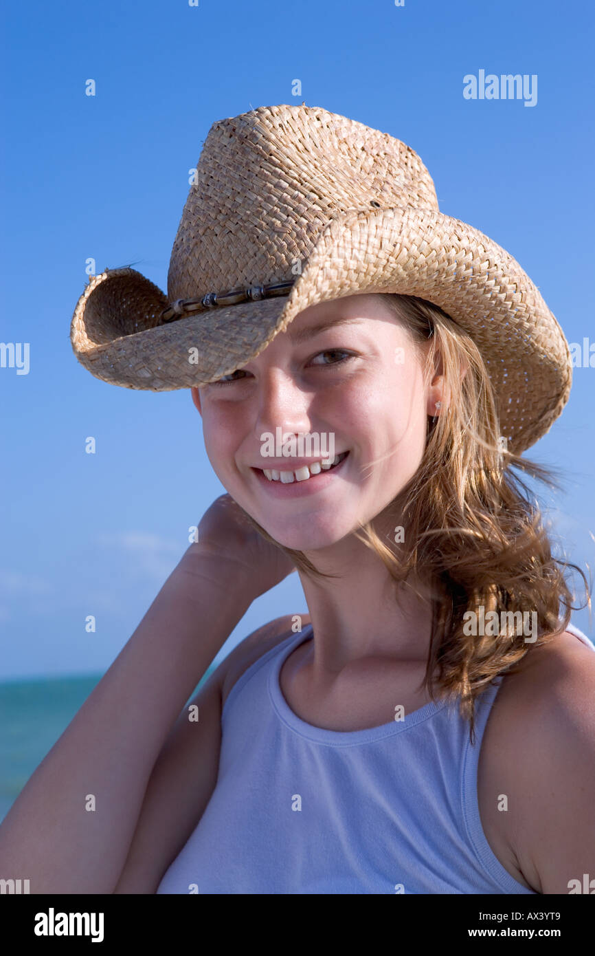 Young caucasian woman wearing straw hat and smiling in Key West, Florida, USA.  Model Released. - Stock Image