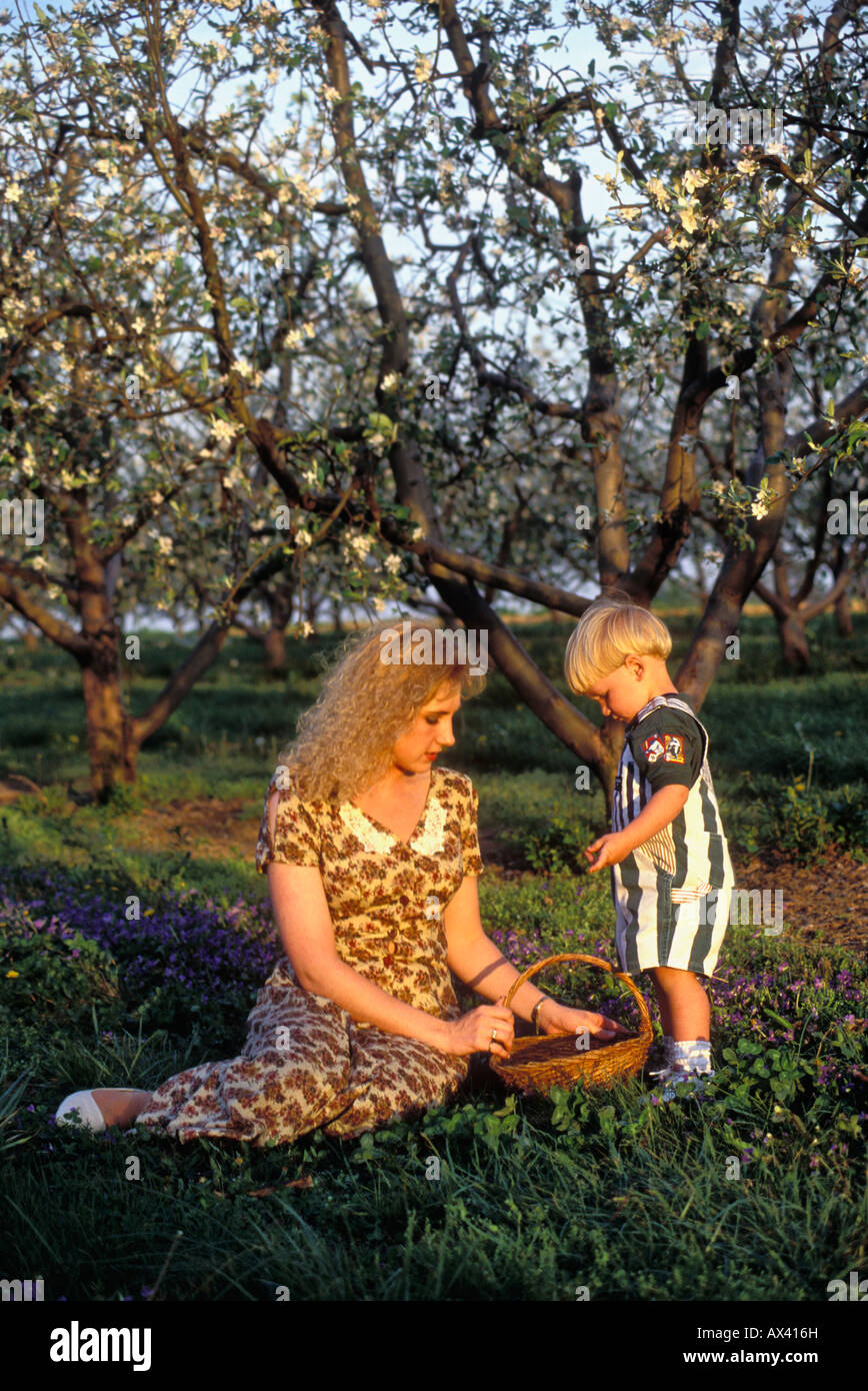 Young Mother and Son in Spring Apple Orchard Stock Photo