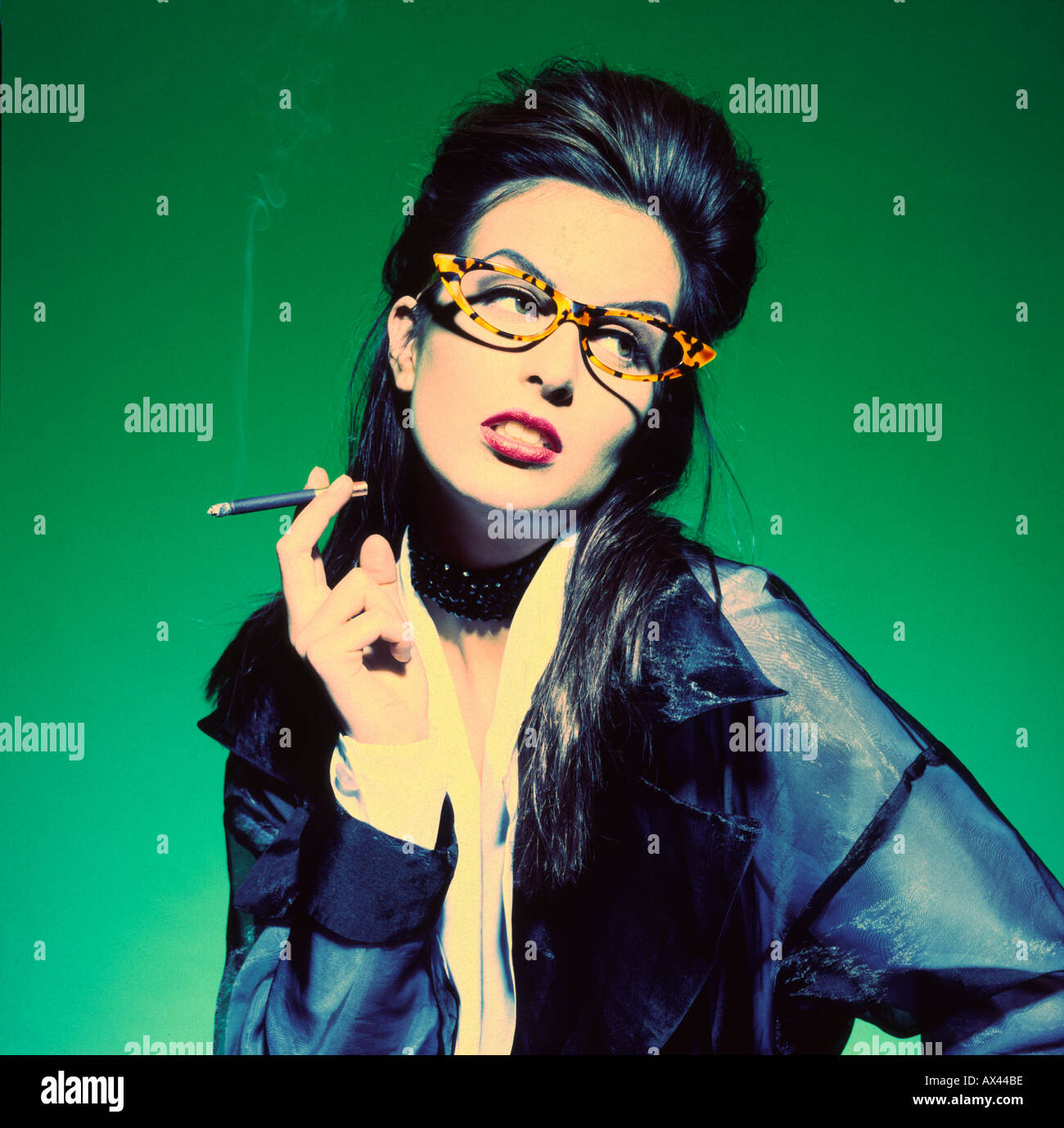 Cool young woman smoking cigarette wearing glasses and looking away - Stock Image