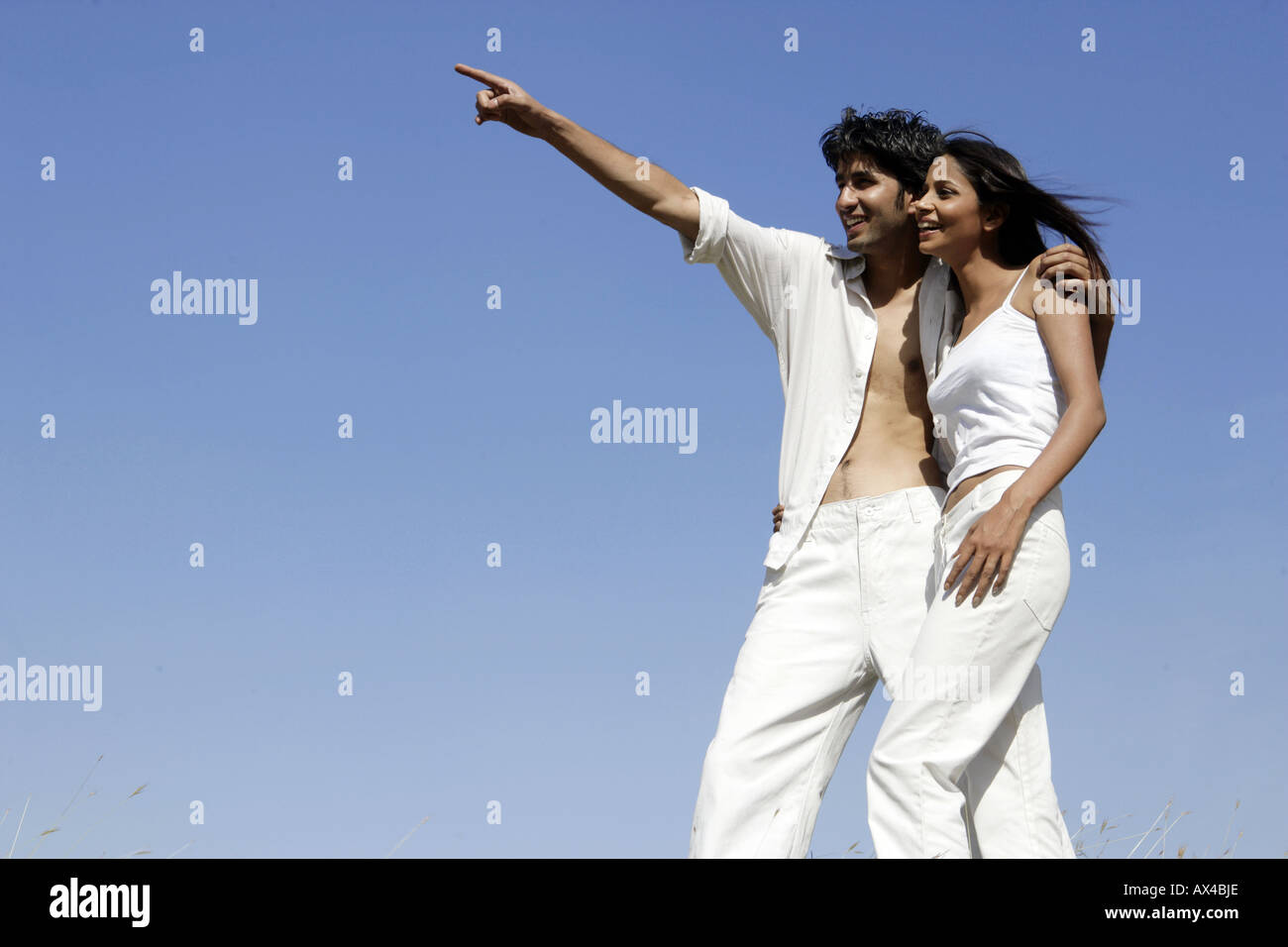 Young man standing with his girlfriend and pointing - Stock Image