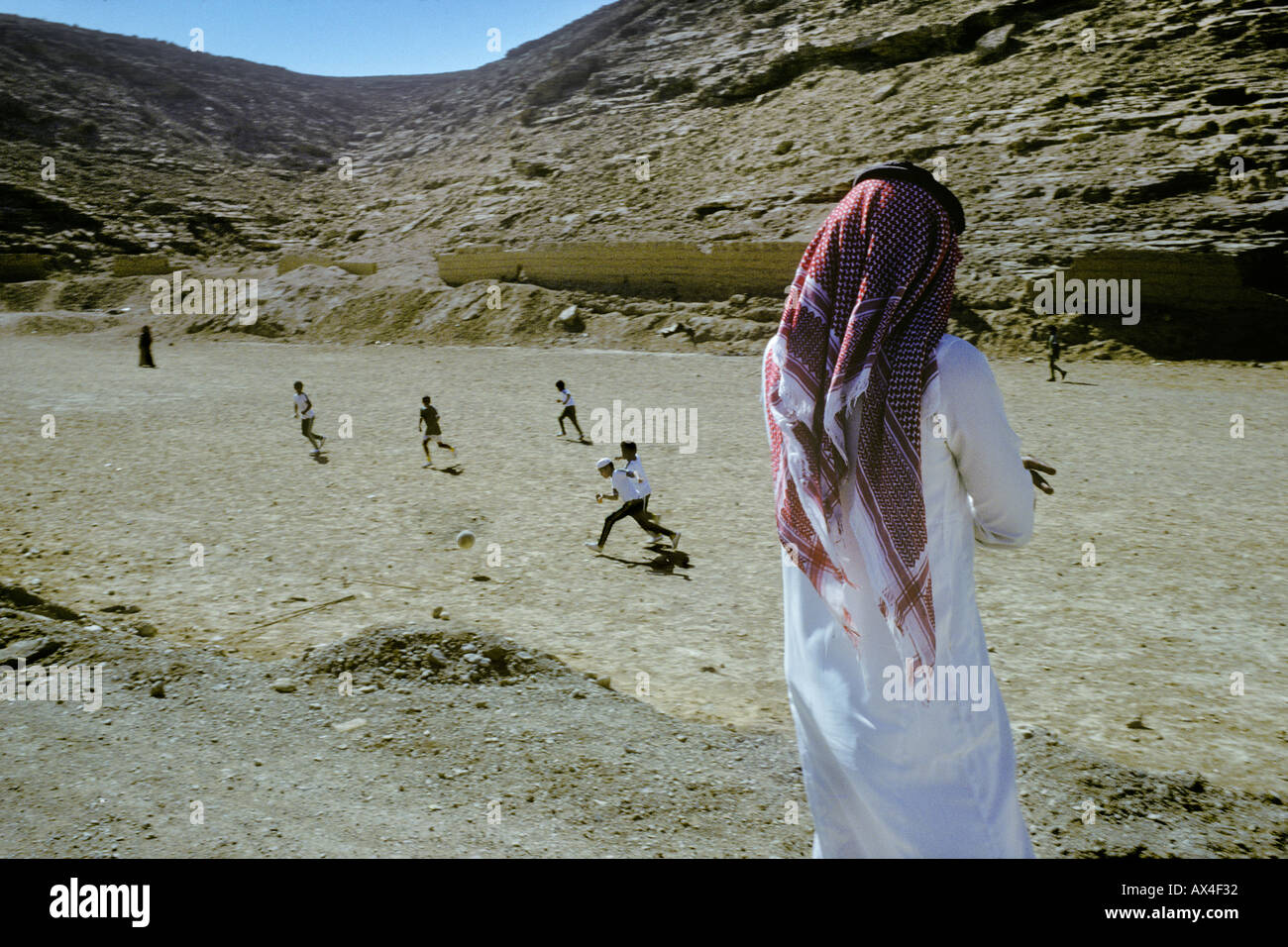 Football on a desert pitch at the edge of a Saudi village - Stock Image