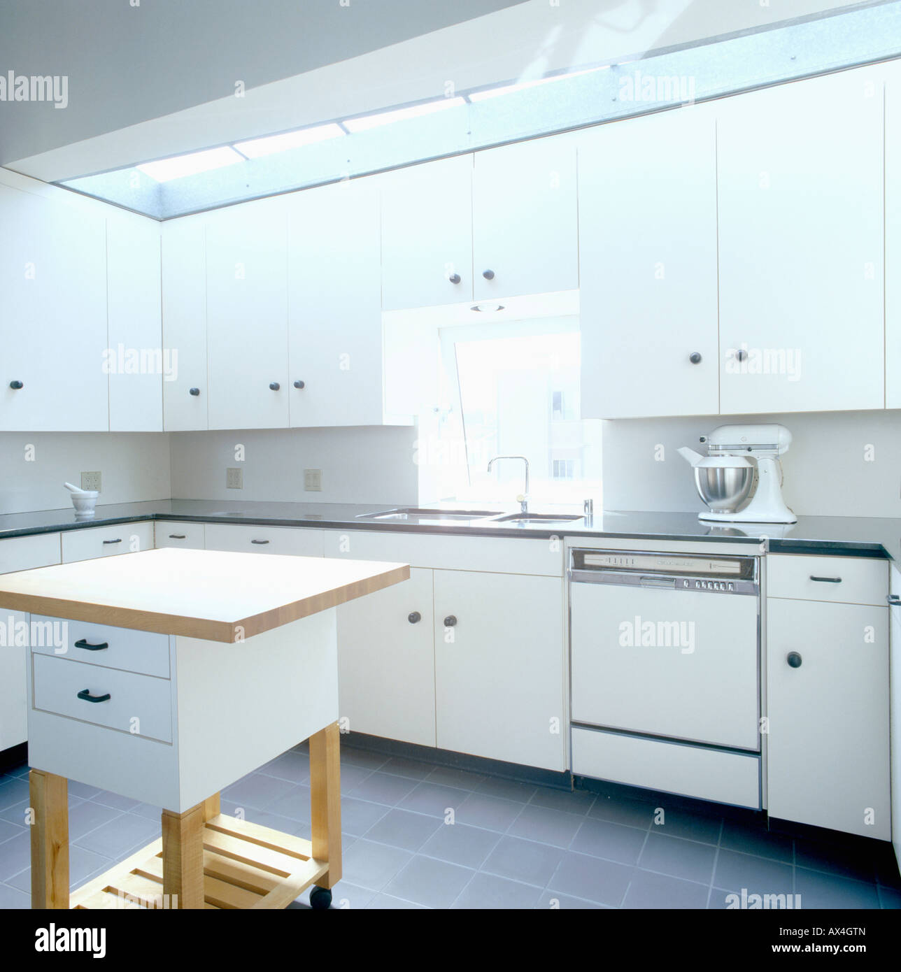 Electric mixer on worktop in modern white streamlined kitchen with ...