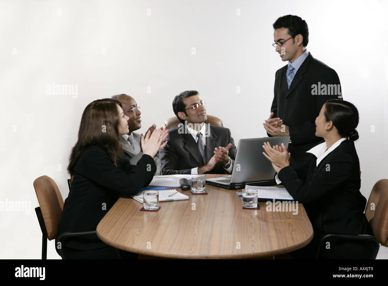 Business team appreciating and clapping their colleague in a boardroom - Stock Image