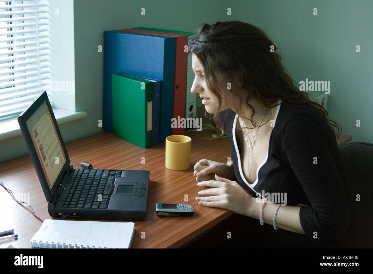 A frustrated woman having problems using a computer - Stock Image