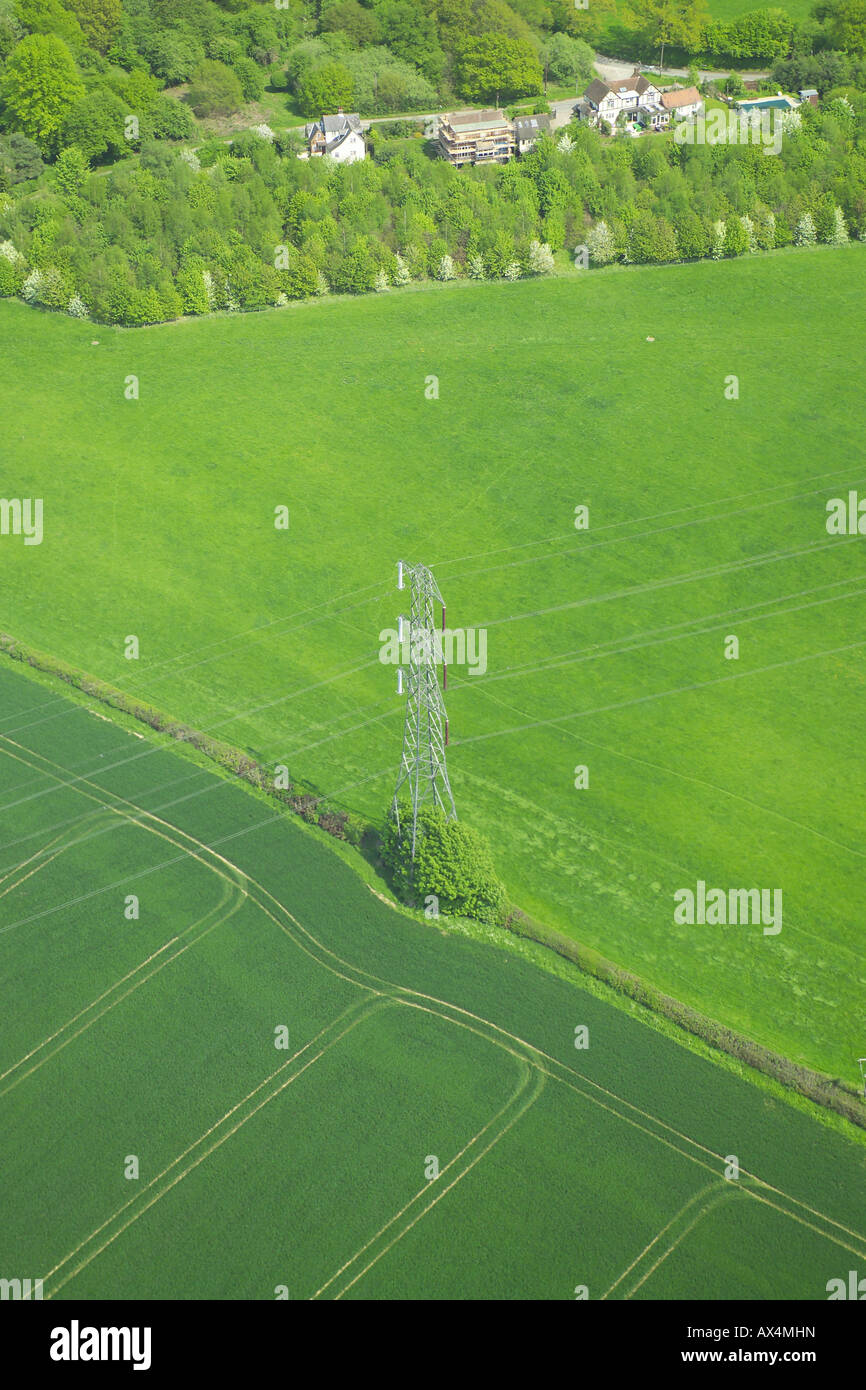 Aerial view of an electricity pylon standing between two fields in a rural setting Stock Photo