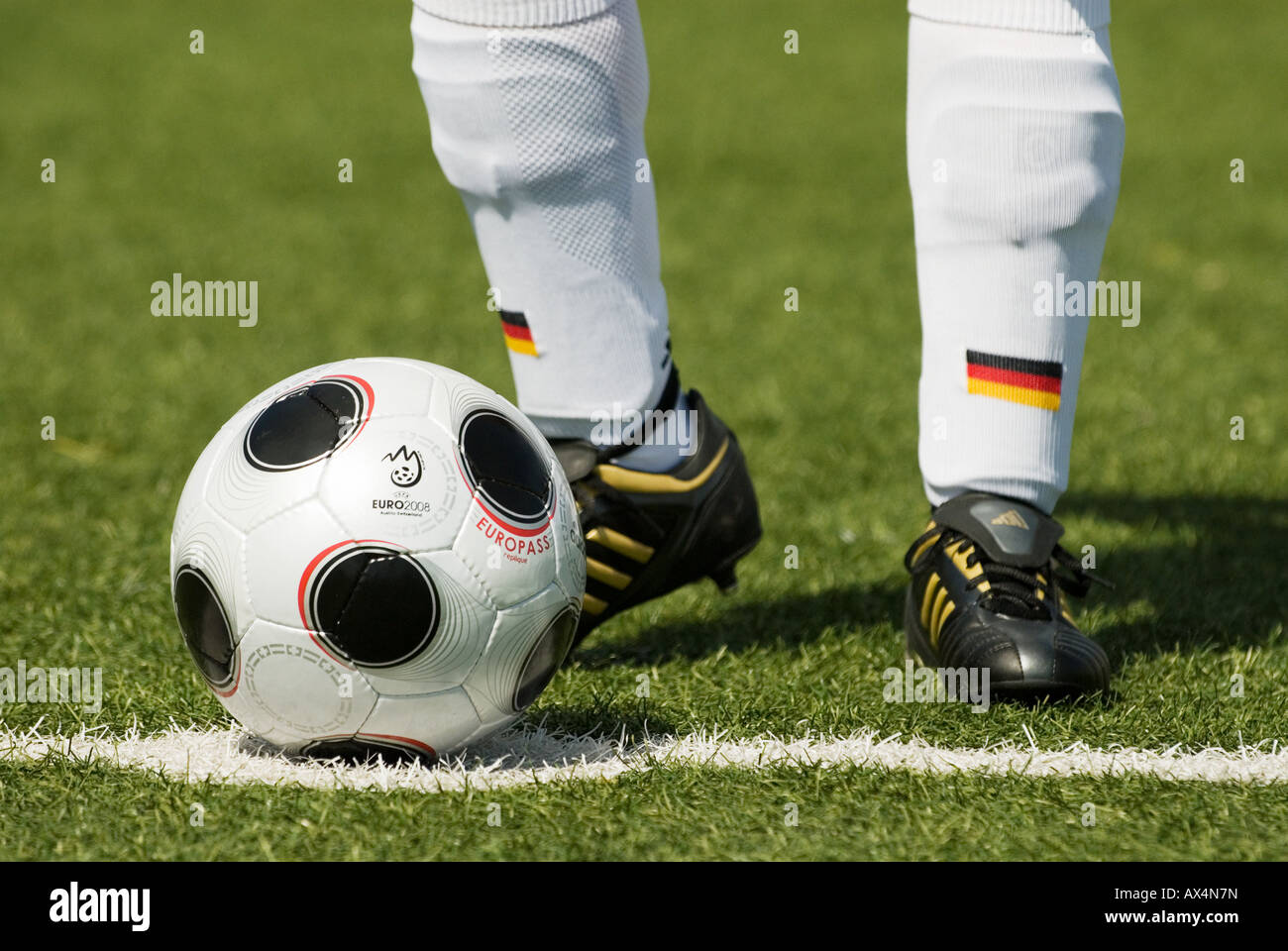 feet of a german national football player stand by a copy of EUROPASS,official matchball of the European football - Stock Image