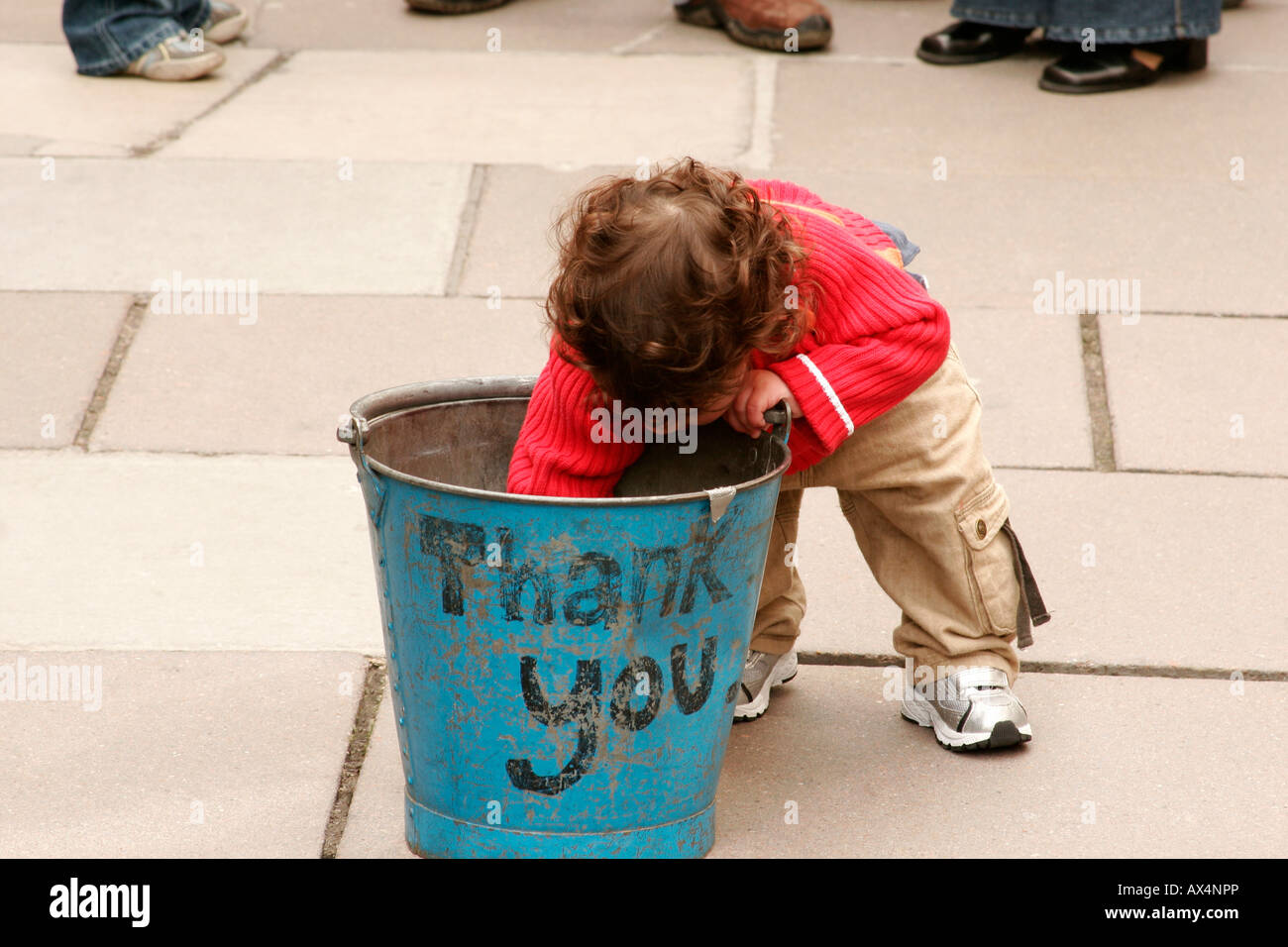 young boy putting money in a busker's bucket, with the words Thank You on the side - Stock Image