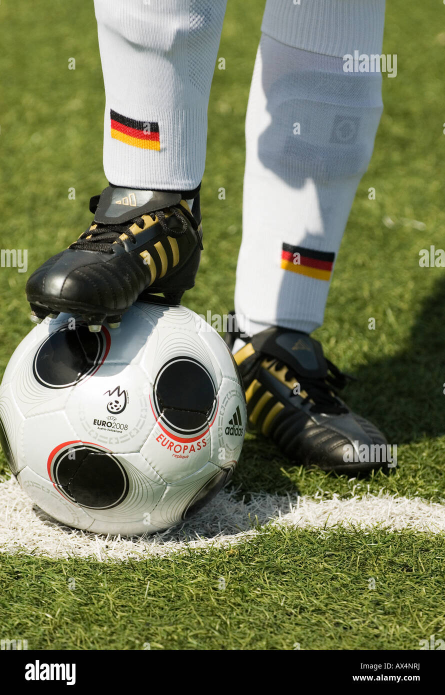 foot of a german national football player stands on a copy of EUROPASS,official matchball of the European football - Stock Image