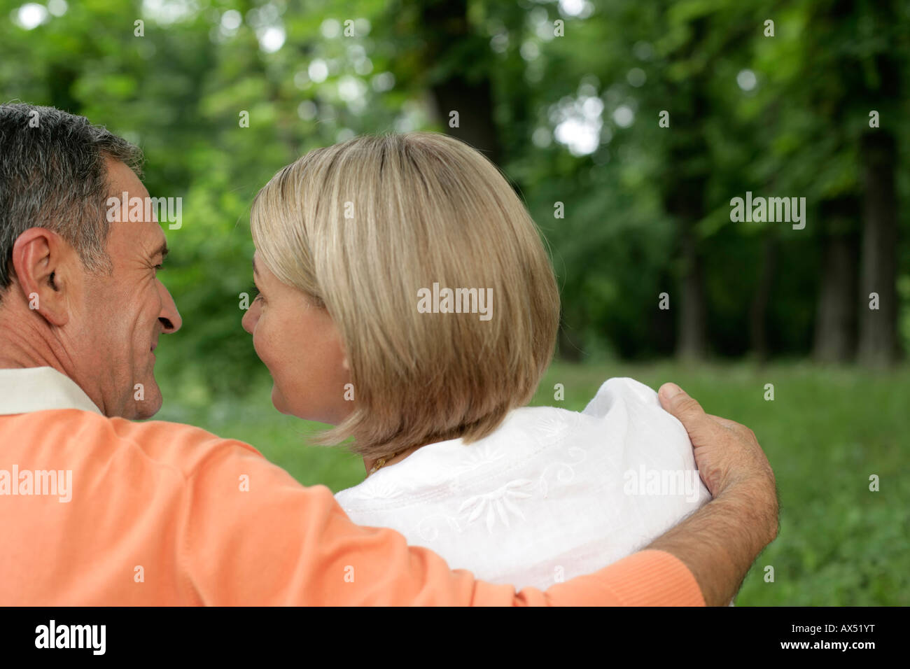 Mature couple embracing each other, looking into each other's eyes - Stock Image