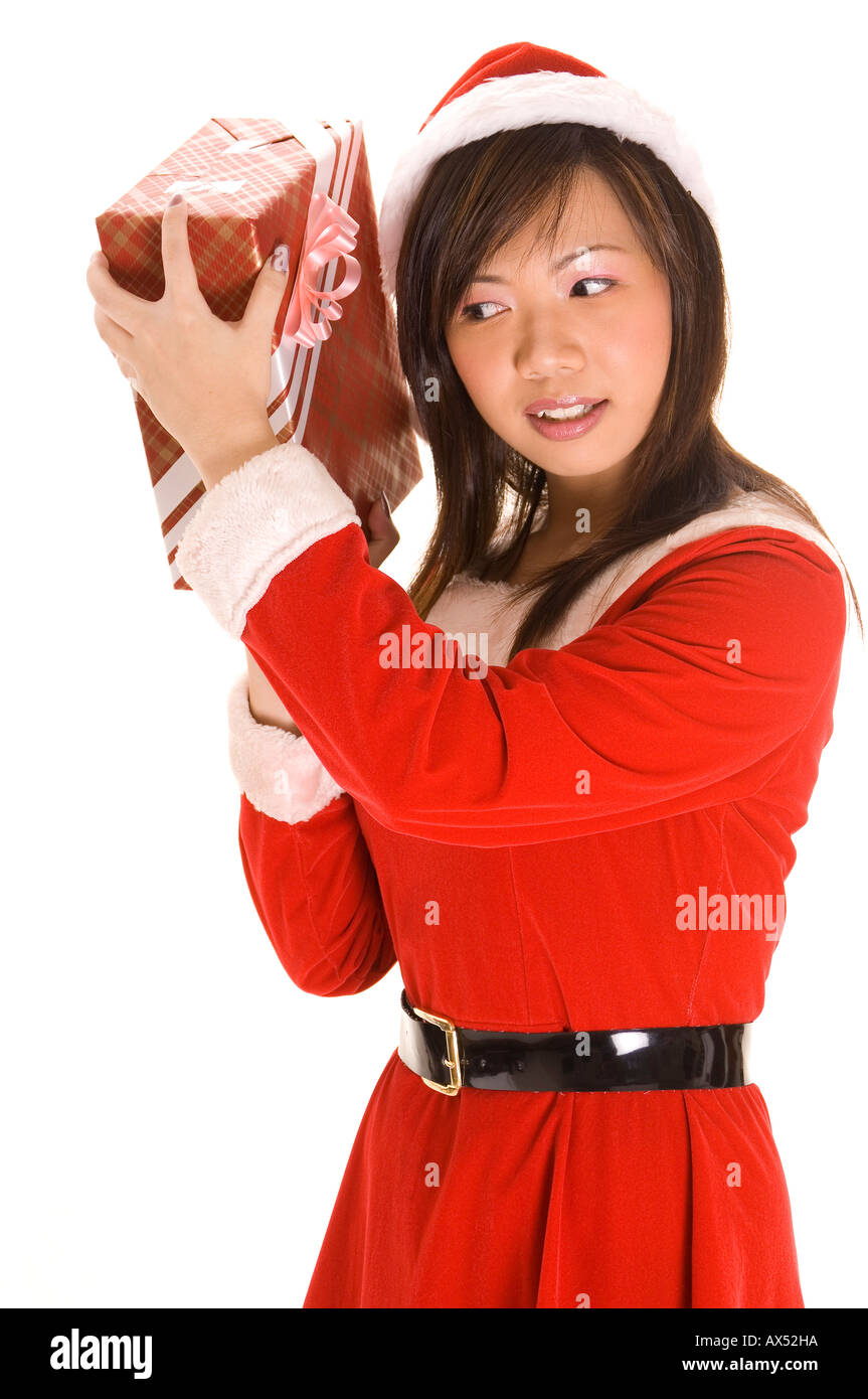 A cute asian woman dressed in a santa costume shakes a present and listens for tell tale signs Stock Photo