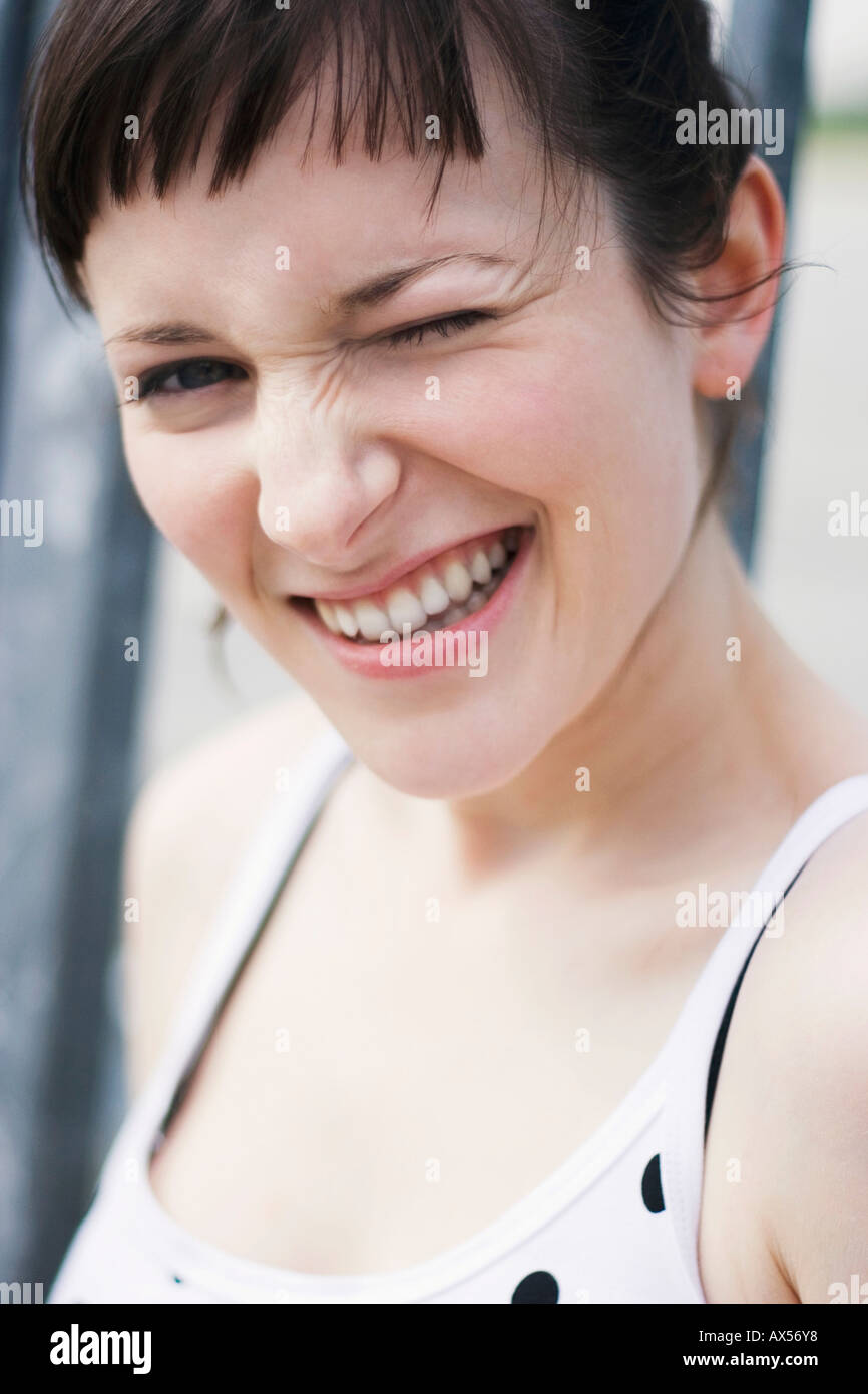 Young woman winking eye, close-up, portrait - Stock Image