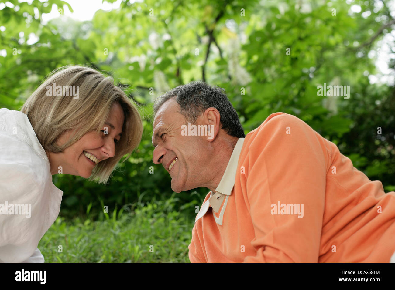 Laughing mature couple lying on grass and looking into each other's eyes - Stock Image