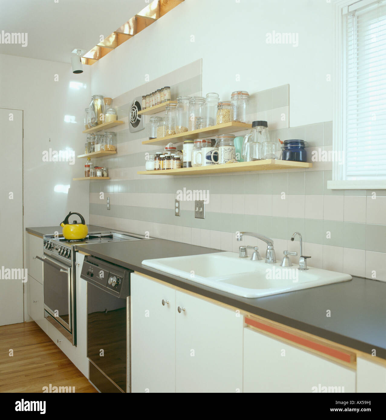 Shelves above double white sink in modern white galley kitchen stock image