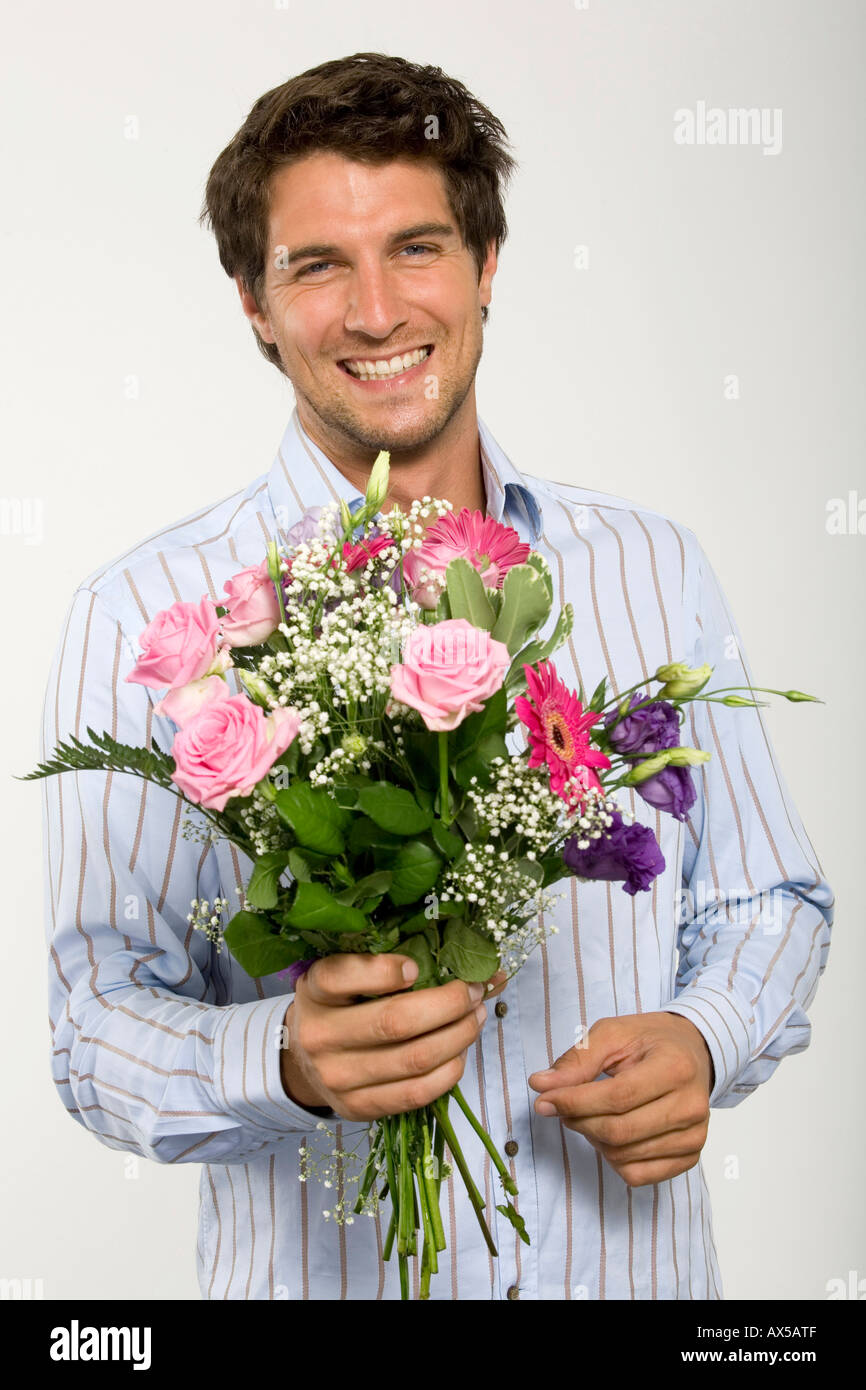 Young man holding bouquet of flowers, smiling, close-up, portrait ...