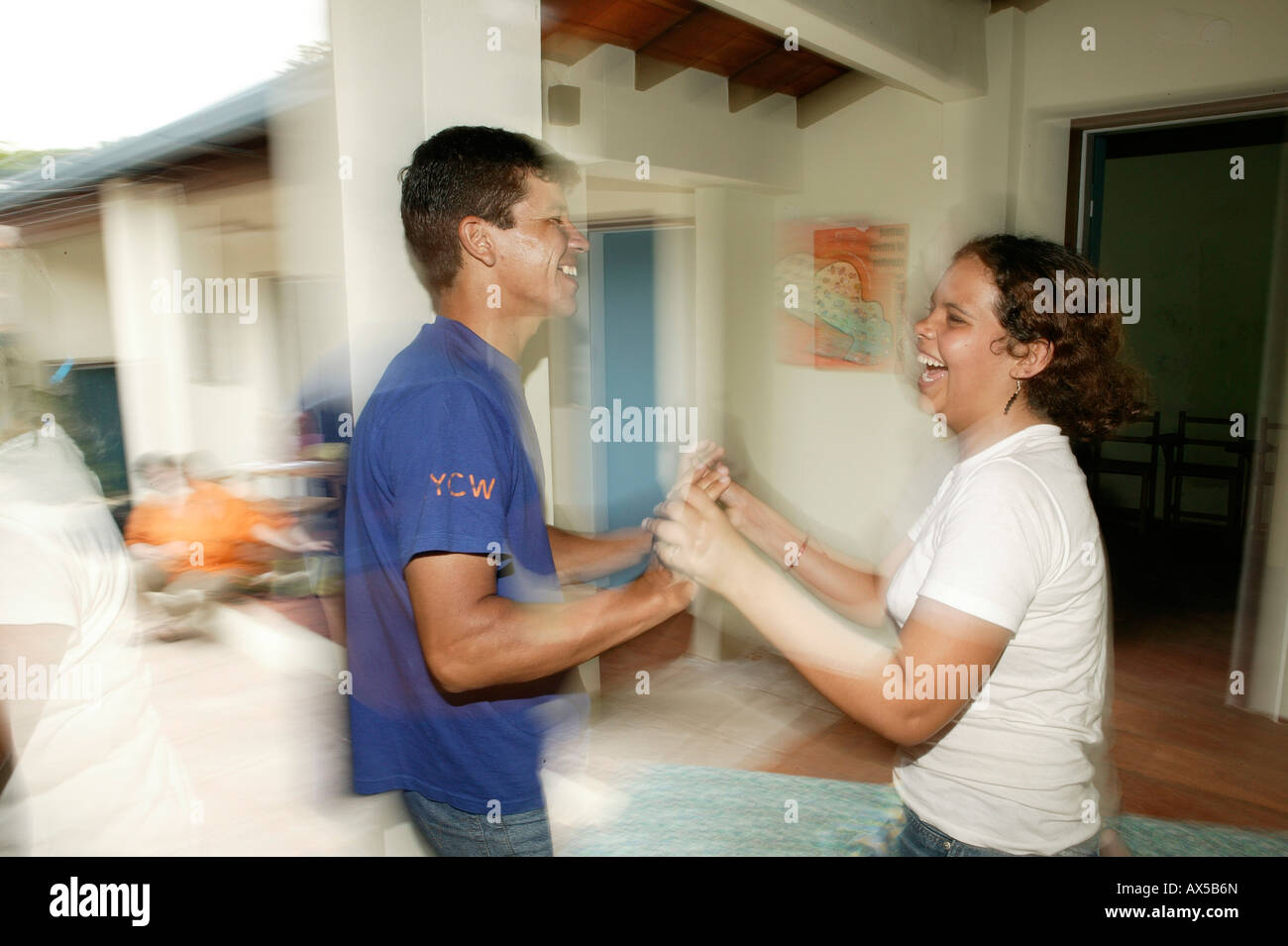 Young woman and man dancing boisterously in front of a house, Asuncion, Paraguay, South America - Stock Image