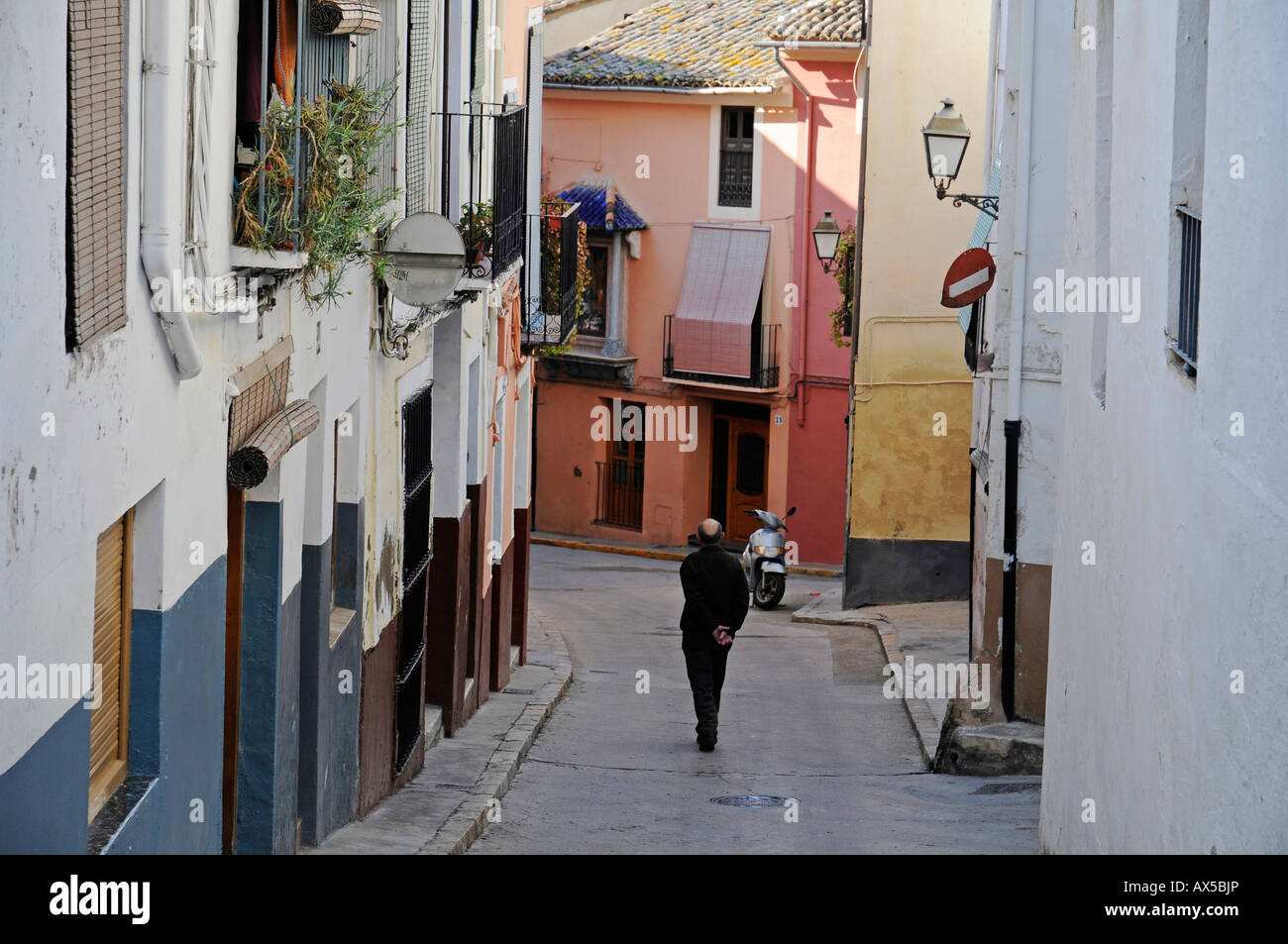 Man walking down a narrow street in the historic centre of Xàtiva (Játiva), Valencia, Spain, Europe - Stock Image