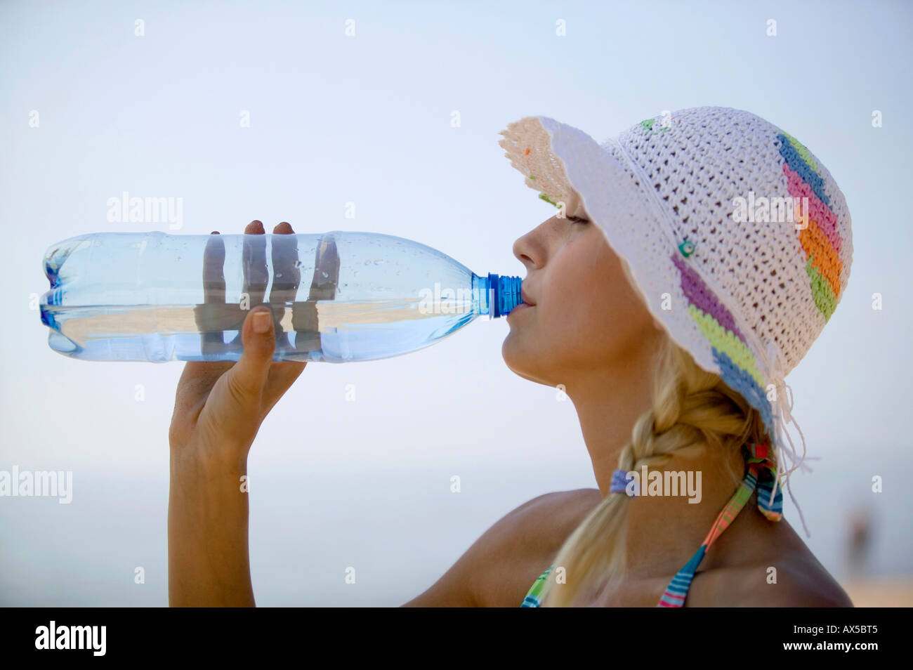 Young woman drinking from water bottle, side view - Stock Image
