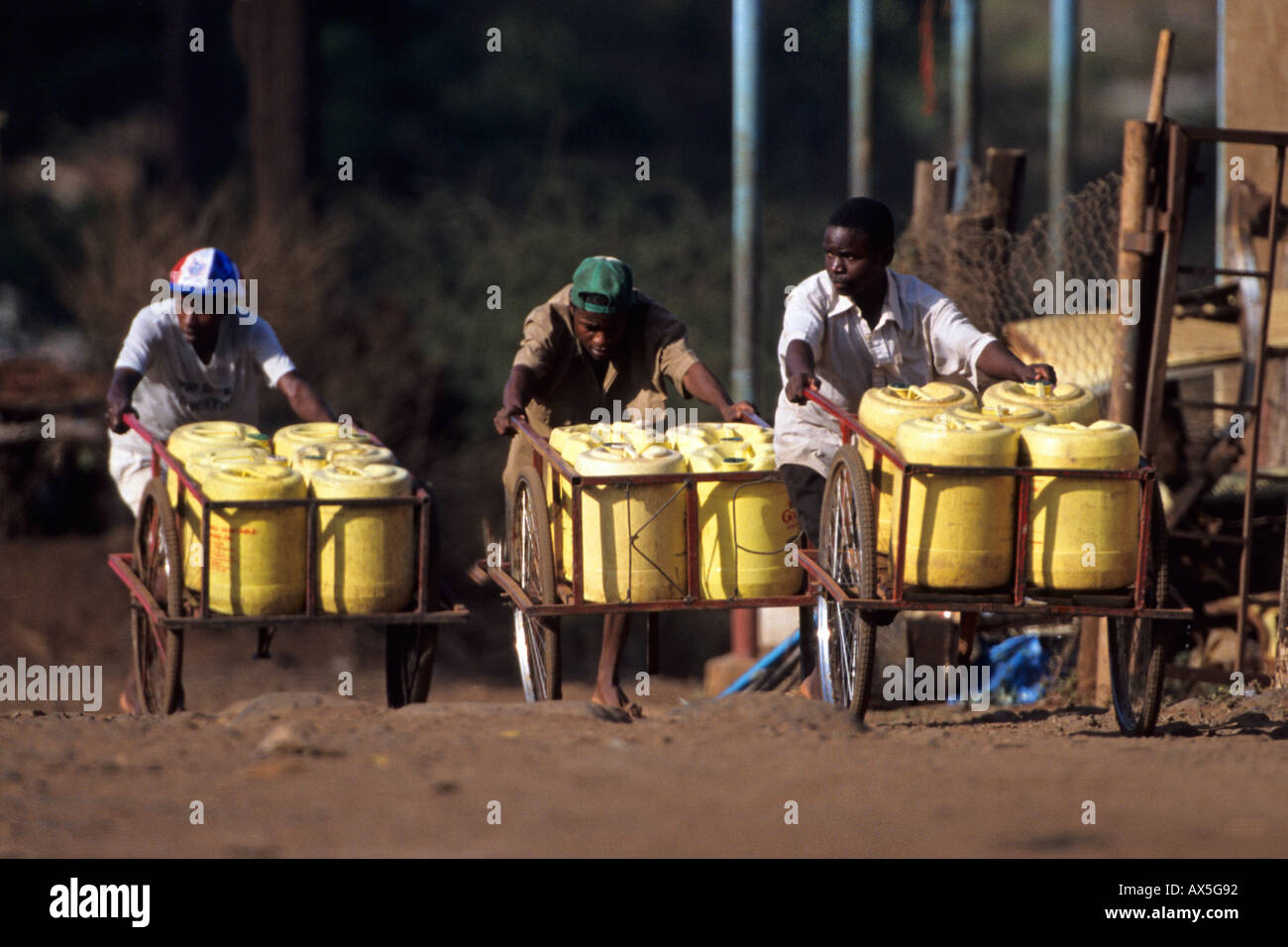 Boys pushing trolleys with drinking water containers for  sale, Himo, Tanzania. Stock Photo