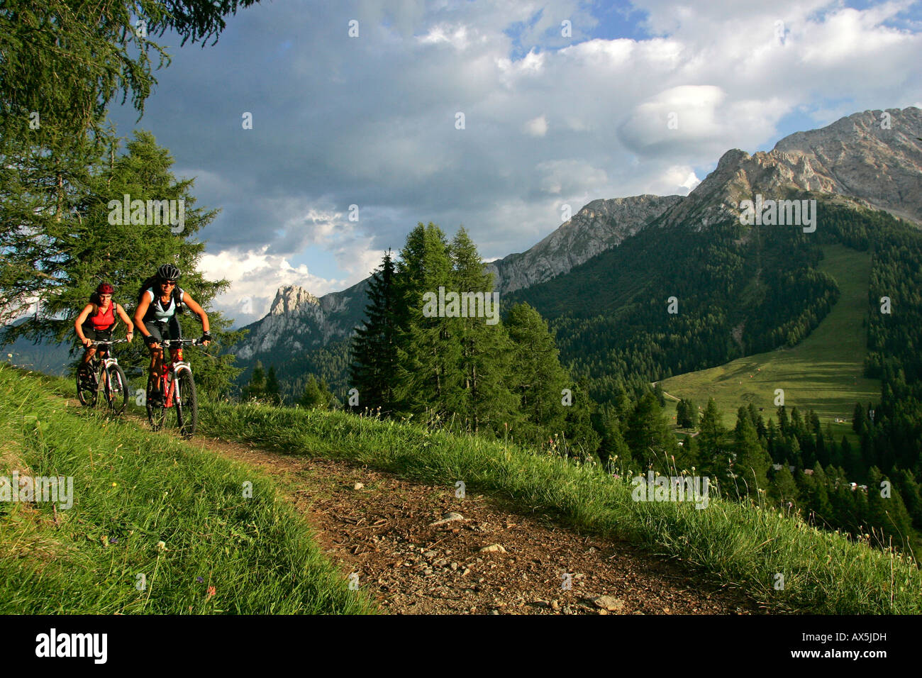 Female mountain bikers cycling through Karer Pass, Dolomites, Northern Italy, Europe - Stock Image