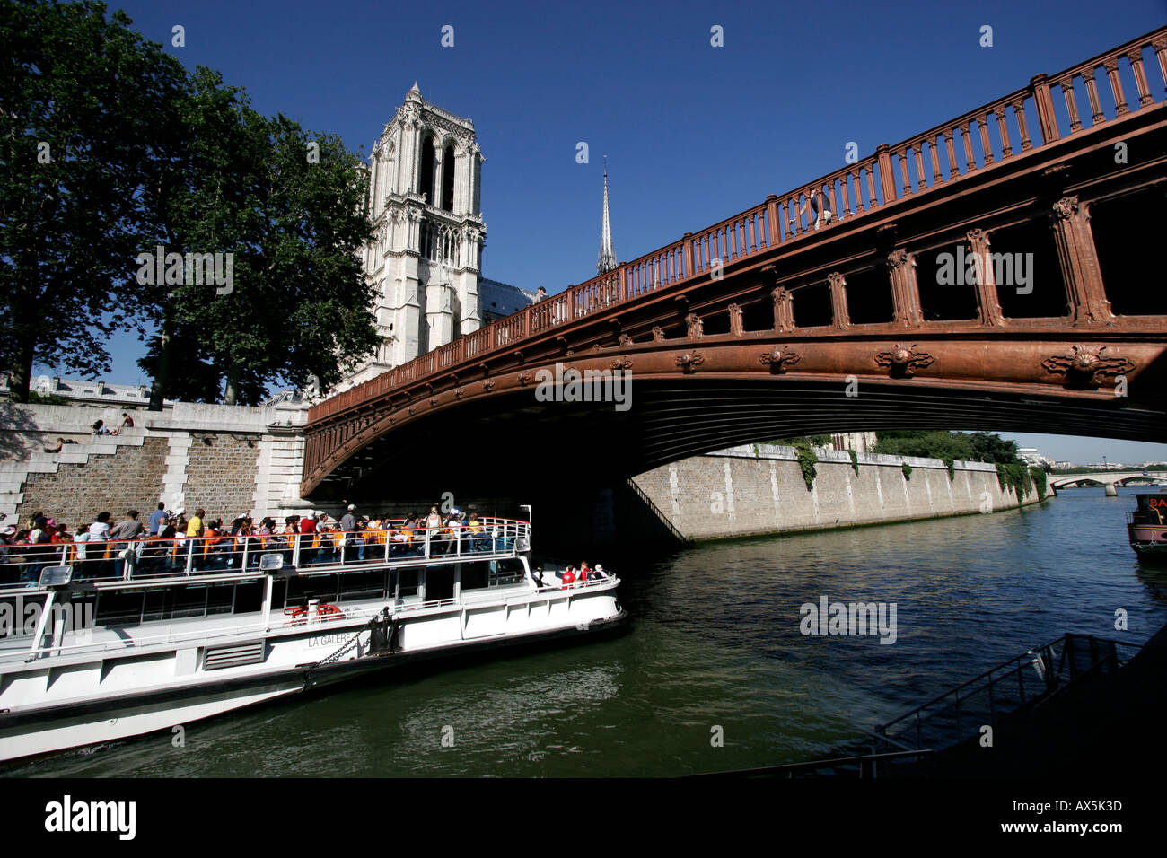 Tour boat under Pont au Double bridge over River Seine with Notre Dame Cathedral in the background Paris, France - Stock Image