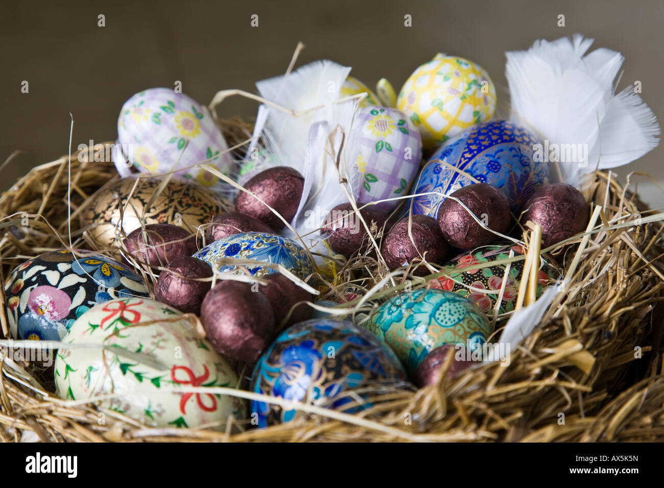 A group of decorated and chocolate eggs arranged in a straw basket a group of decorated and chocolate eggs arranged in a straw basket as an easter decoration surrey england negle Choice Image