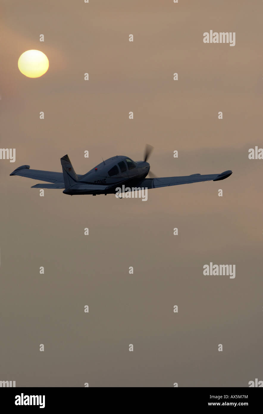 Piper aircraft flying in the evening sun over the ocean (composite shot), Egelsbach, Hesse, Germany, Europe - Stock Image