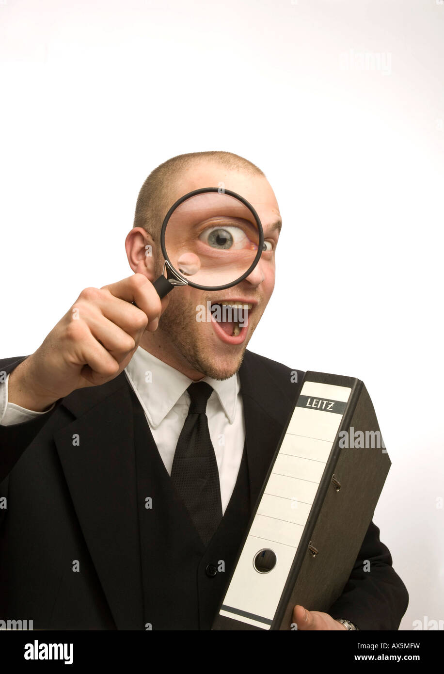 Young man carrying binder holding magnifying glass in front of his face Stock Photo