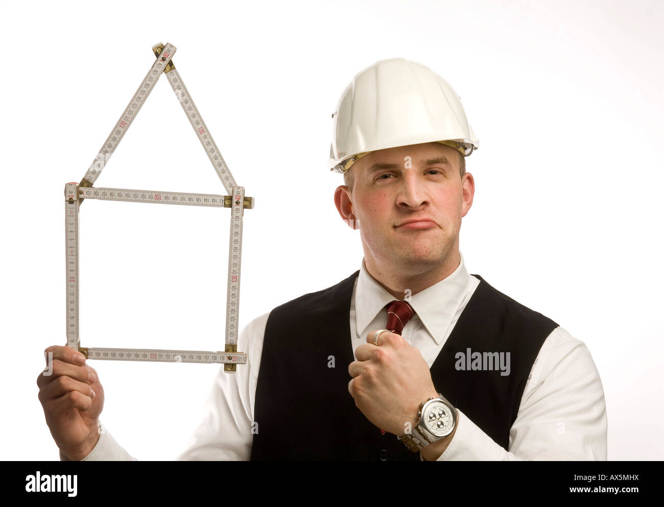Man dressed in suit holding yardstick shaped into a house - Stock Image