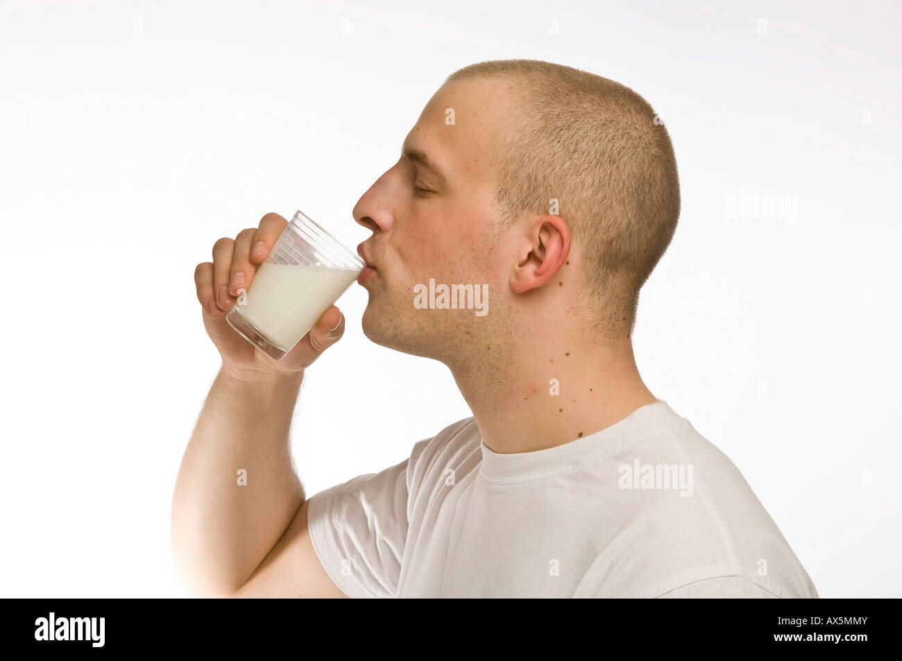 Young man drinking a glass of milk Stock Photo