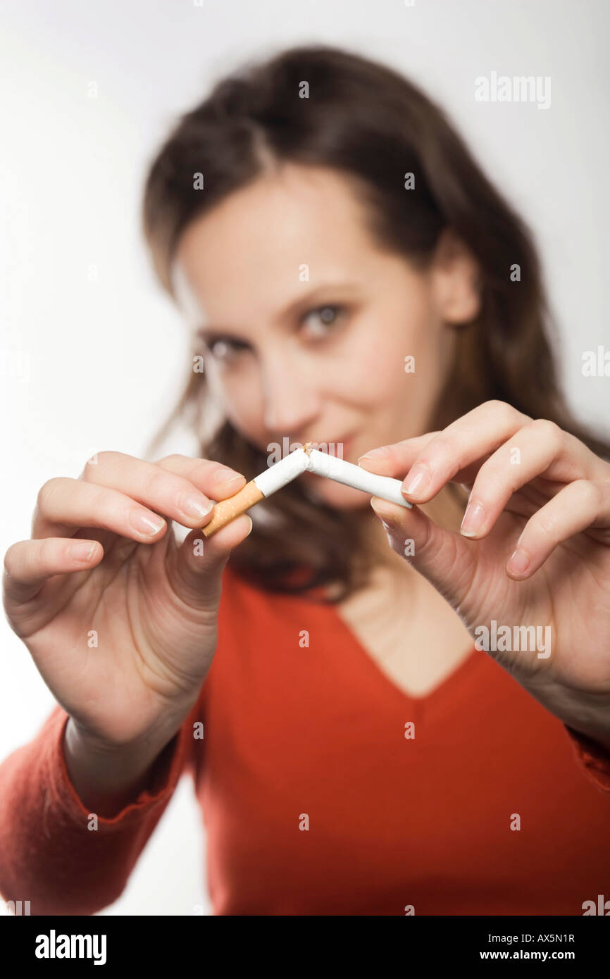 Young woman breaking a cigarette in half Stock Photo