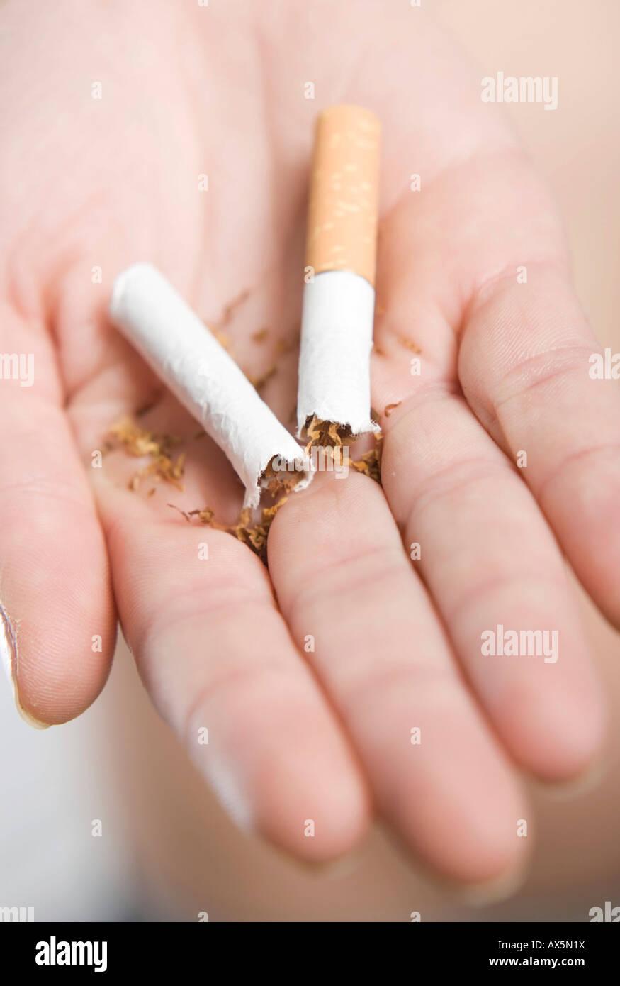 Hand holding a cigarette broken in half Stock Photo