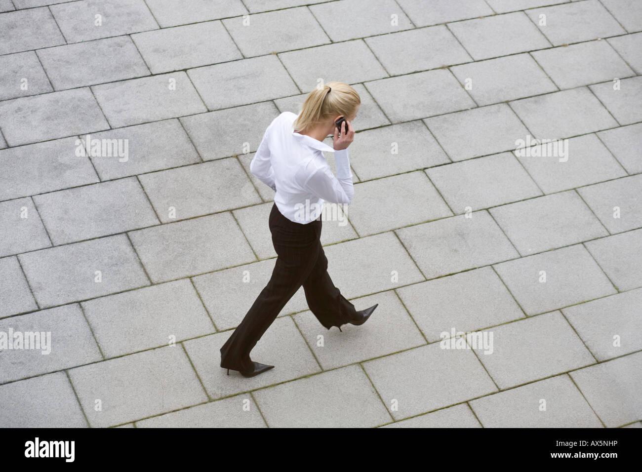 Businesswoman talking on phone as she walks Stock Photo