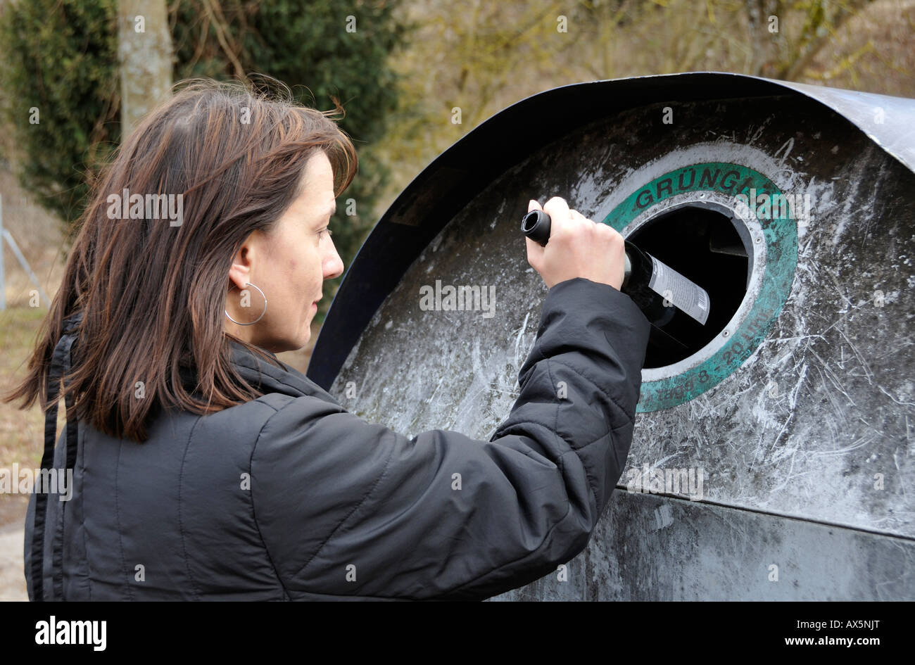 Woman is throwing a bottle in a German bottle bank (Glascontainer) - Stock Image
