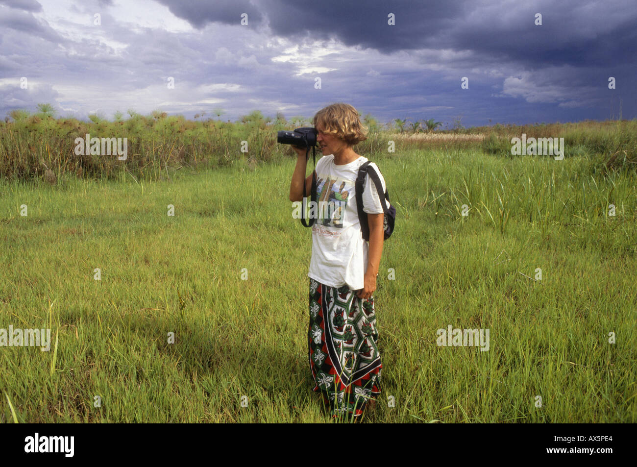 Zambia, Africa. Woman tourist with Olympus camera taking a picture in papyrus reed wetland. - Stock Image