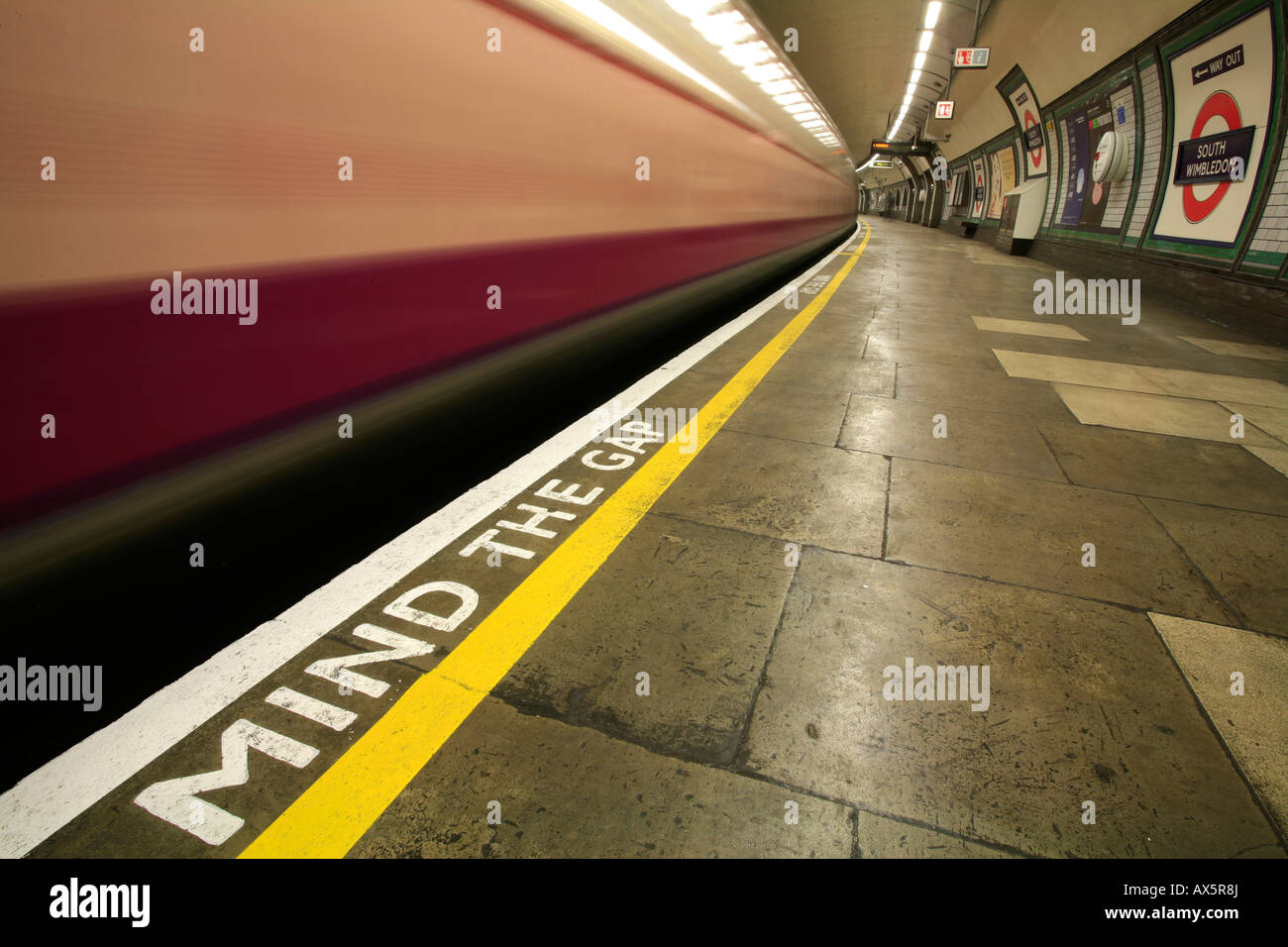Mind the Gap - safety reminder and train coming through South Wimbledon underground station, London, England, UK, - Stock Image