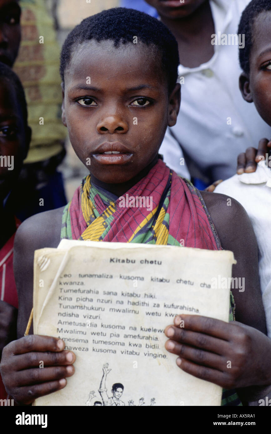 Ninde, Tanzania. Child in colourful cotton print wrap dress holding a book written in Swahili. - Stock Image