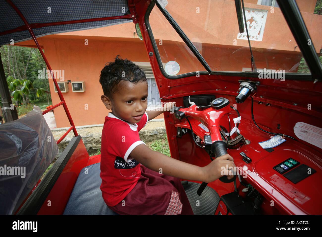 Small boy sitting at the wheel of a tuk-tuk in Hanwella, Sri Lanka, South Asia Stock Photo