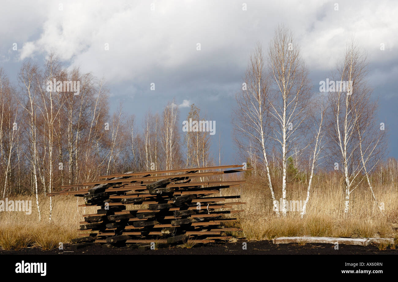 Disassembled railroad tracks stacked in a former peat working area, Nicklheim, Bavaria, Germany, Europe - Stock Image