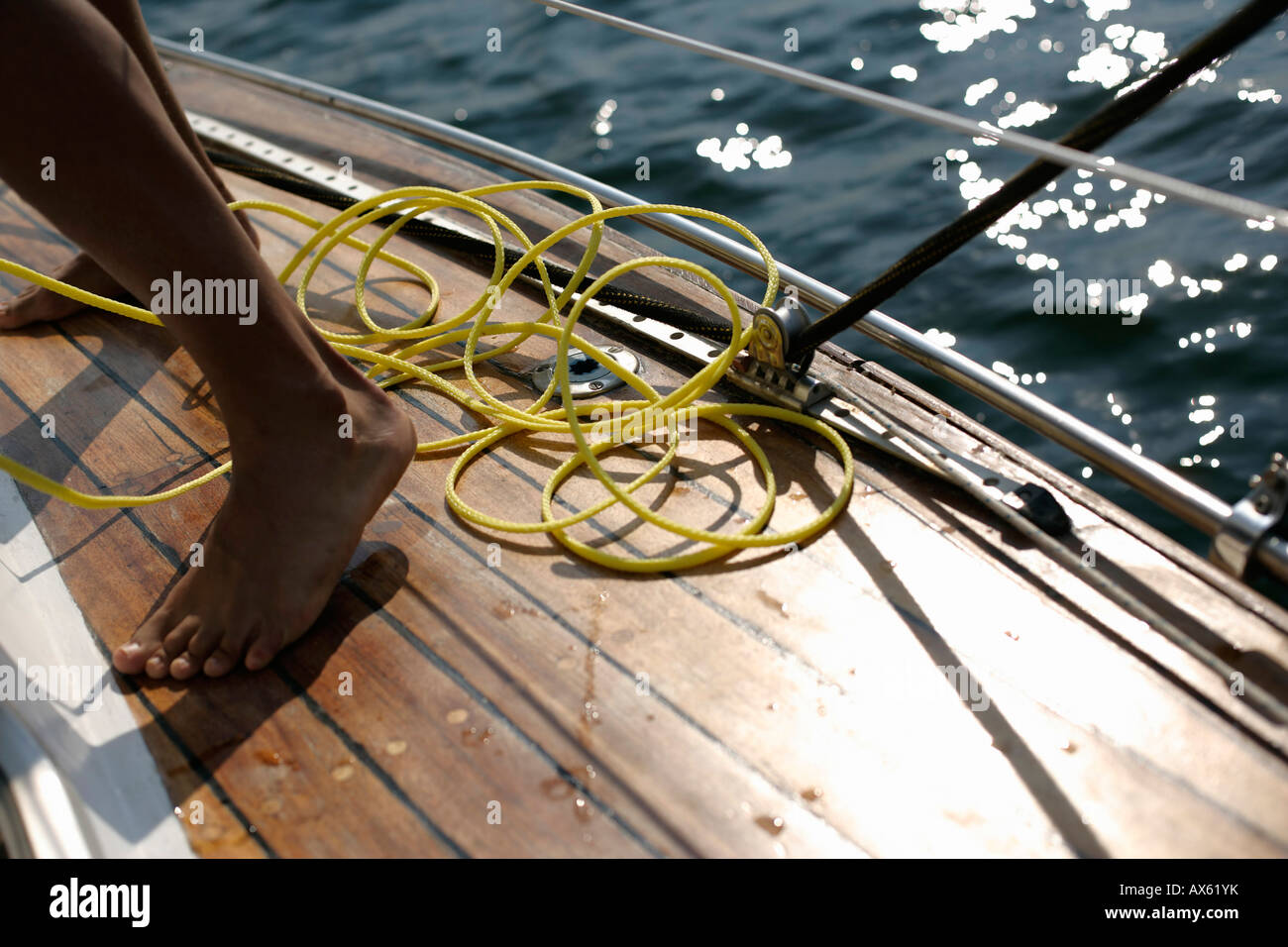 Yellow line between the feet of a man on deck - Stock Image