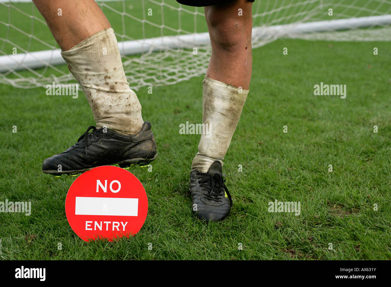Soccer player's foot on a 'no entry' label - Stock Image