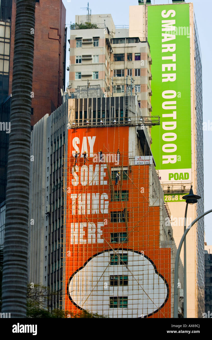 Bamboo Scaffolding Billboard Advertising on the Wall of a Building in Hong Kong - Stock Image