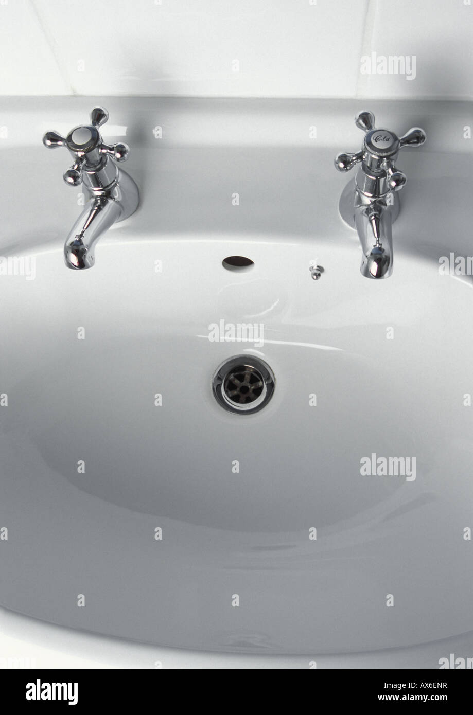 Traditional chrome taps on white bathroom sink basin - Stock Image