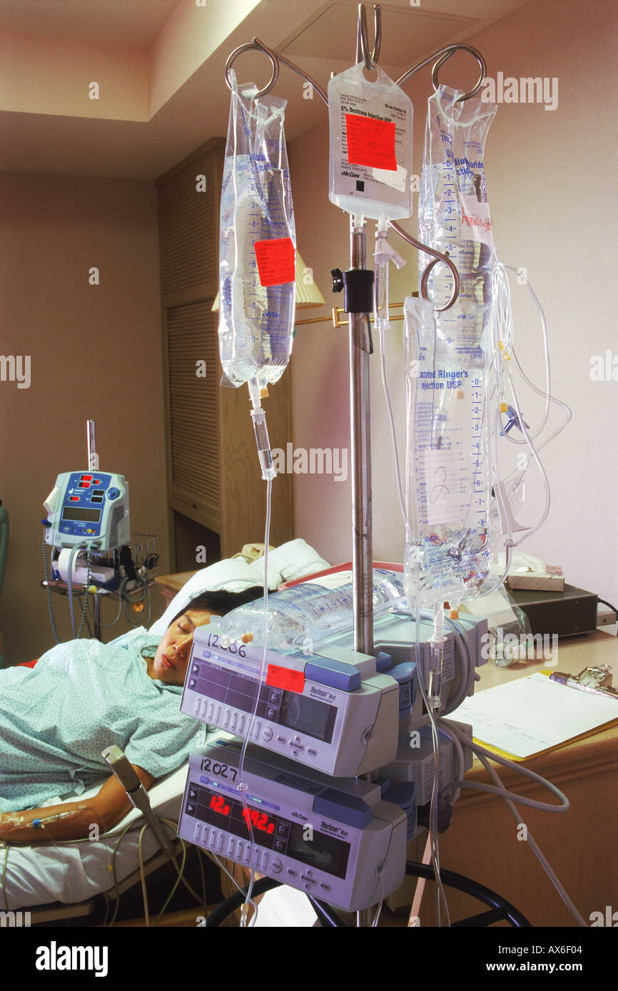 Woman connected to IV tubes in hospital recovery room Stock Photo