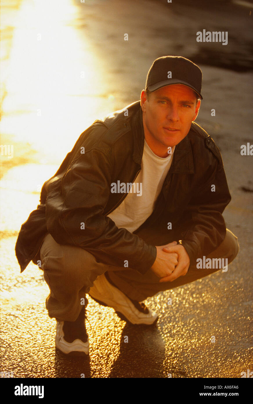 92feb53ee81 Portrait of a man wearing baseball cap in squatting position Stock ...