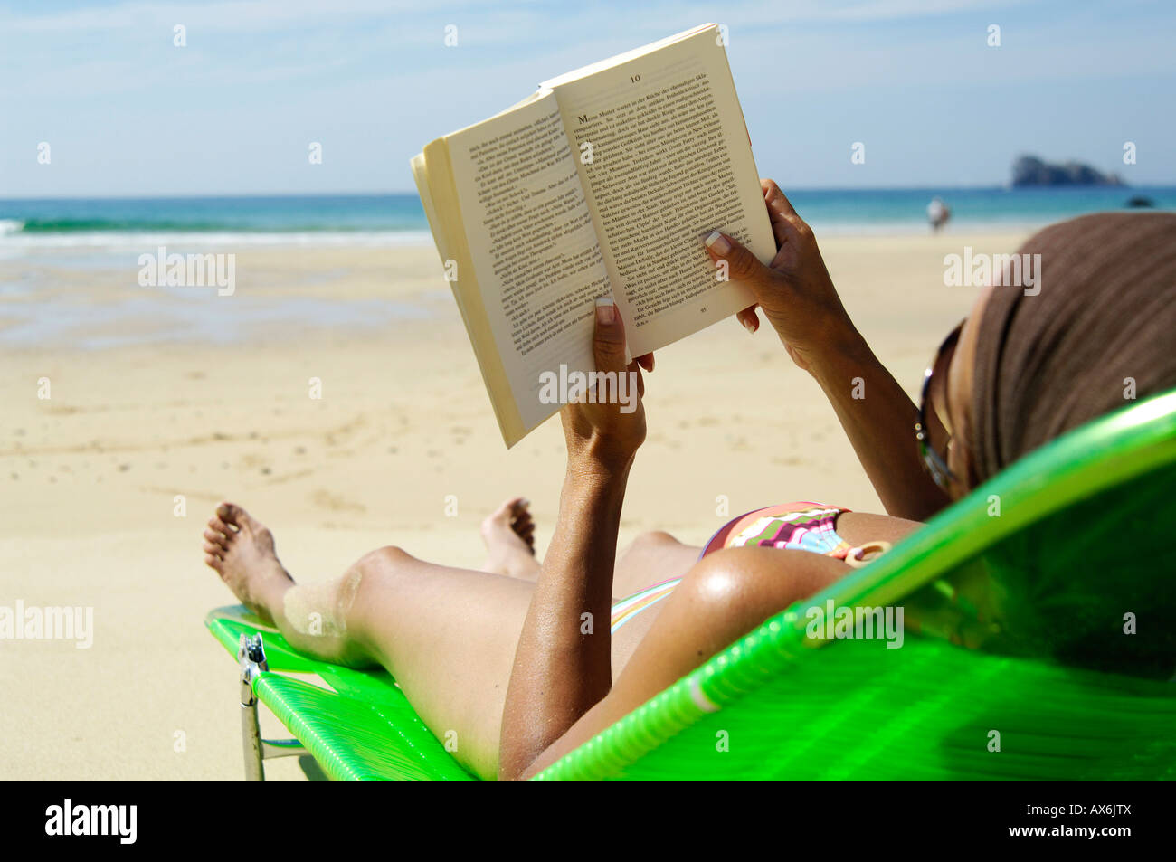 Rear view of woman reading book on beach chair - Stock Image