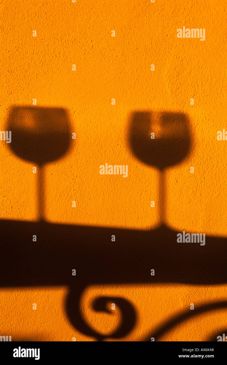 Silhouette of two wine glasses on wrought a iron table. Late afternoon sun - Stock Image