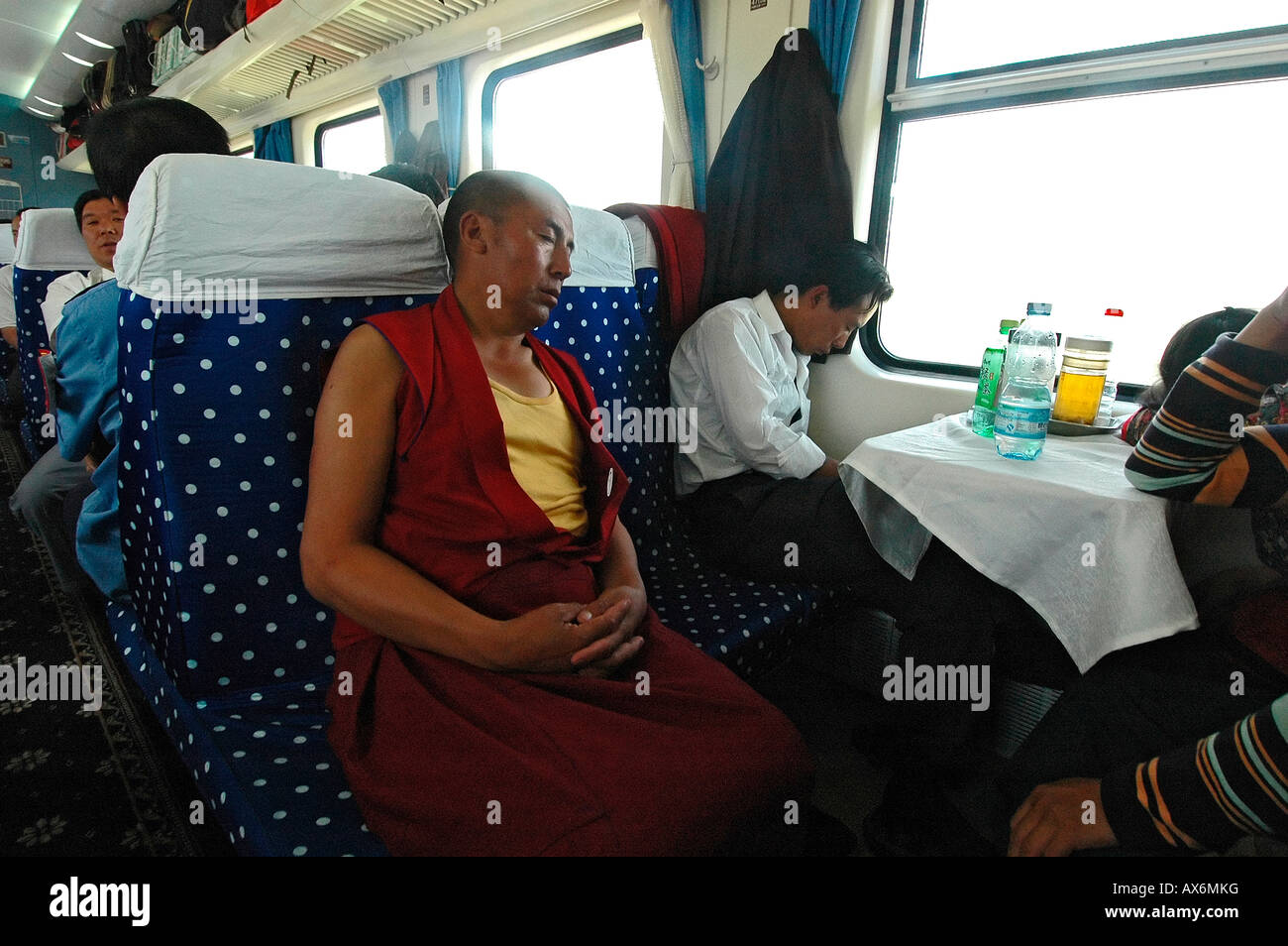 A monk sleeps on the Tibet train Tibet railway - Stock Image