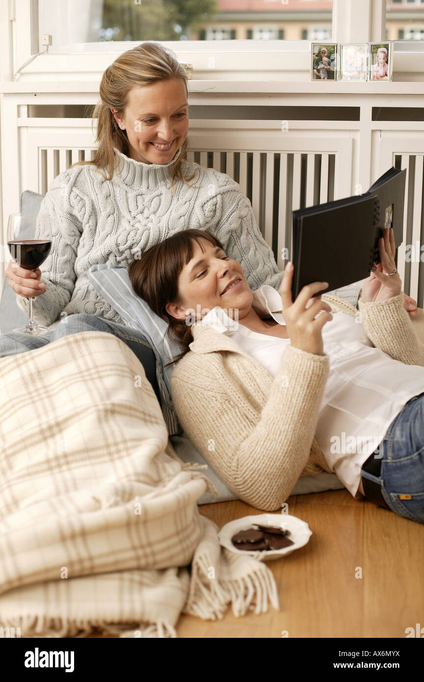 Woman and her daughter looking at photo album and smiling - Stock Image
