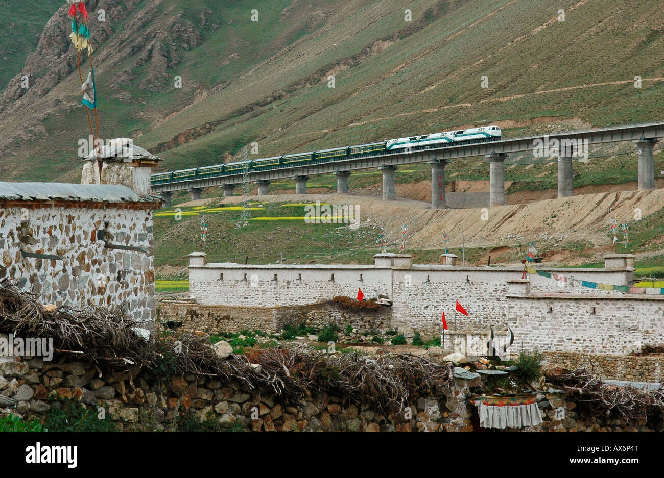 A train passes over a bridge next to a Tibetan village on the Tibet railway, which opened in July 2006. Tibet train - Stock Image